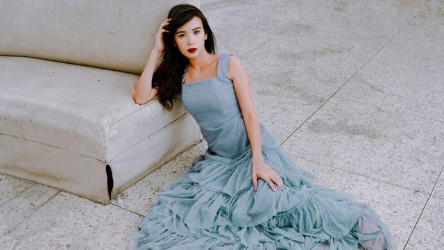 Dívka v modrých společenských šatech sedící na zemi