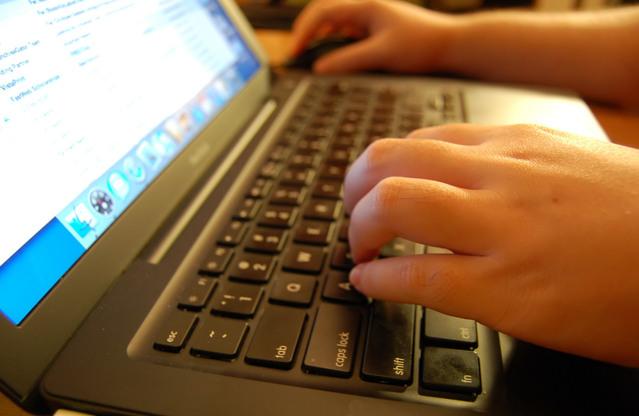 otevřený notebook, ruce na klávesnici a na myši, otevřené stránky